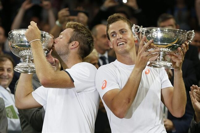 Vasek Pospisil of Canada, right, and Jack Sock of the U.S hold their trophies after defeating Bob Bryan and Mike Bryan of the U.S in the men's doubles final at the All England Lawn Tennis Championships in Wimbledon, London, Saturday July 5, 2014. Pospisil has usually just played a little doubles on the side throughout his tennis career. That will change now that he's a Wimbledon champion. THE CANADIAN PRESS/AP/Sang Tan