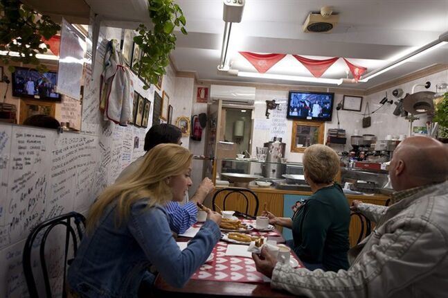 People eat breakfast as they watch Spain's newly crowned King Felipe VI accompanied by Queen Letizia on a television in a bar in Pamplona, northern Spain, Thursday, June 19, 2014. Felipe's father Juan Carlos, who reigned during four decades, stepped down after signing an abdication law Wednesday so that younger royal blood can rally a country beset by economic problems, including an unemployment rate of 25 percent. (AP Photo/Alvaro Barrientos)