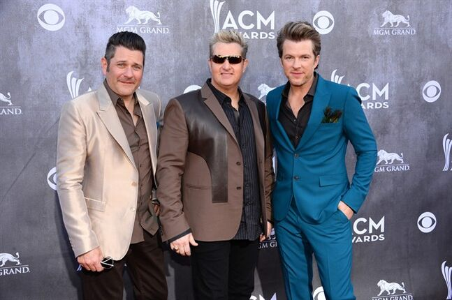 FILE - In this April 6, 2014 file photo, from left, Jay DeMarcus, Gary LeVox and Joe Don Rooney, of the musical group Rascal Flatts, arrive at the 49th annual Academy of Country Music Awards at the MGM Grand Garden Arena, in Las Vegas. Rascal Flatts later apologized for lip-synching during their performance at the Academy of Country Music Awards.( Photo by Al Powers/Powers Imagery/Invision/AP, file)