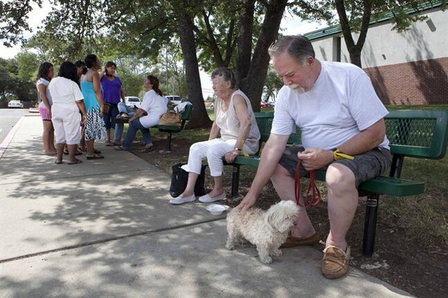 Sand Fire evacuees Doc Bassett, and his neighbor Bev Matson take care of his dog Sophie while waiting for fire updates from officials at the evacuation center in Shingle Springs, Calif., on Monday, July 28, 2014. (AP Photo/Steve Yeater)