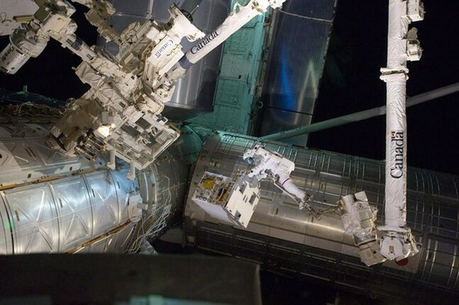 In this Tuesday, July 12, 2011 photo made available by NASA, astronaut Ron Garan rides on the International Space Station's robotic arm as he transfers a failed pump module to the cargo bay of space shuttle Atlantis. A new study says Canada has experienced a small bounce in its space competitiveness and retains a skilled workforce but is still facing future challenges. THE CANADIAN PRESS/AP, NASA