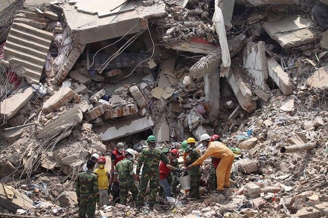 Workers try to release two bodies trapped in the rubble of collapsed Rana Plaza garment factory building in Savar, near Dhaka, Bangladesh, April 30, 2013. More than 1,100 garment workers were killed in the Bangladesh factory collapse in April. THE CANADIAN PRESS/AP-Wong Maye-E, File