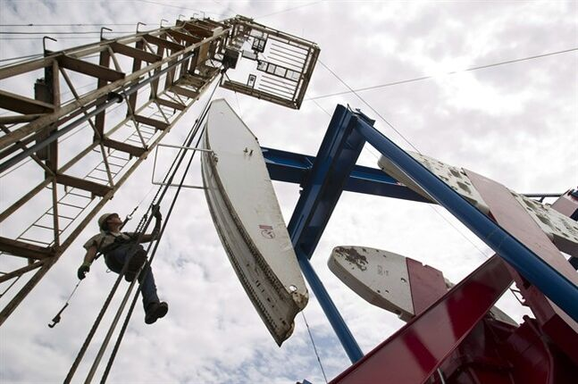 A worker hangs from an oil derrick outside of Willisburg, N.D. on July 26, 2011. THE CANADIAN PRESS/AP, Gregory Bull
