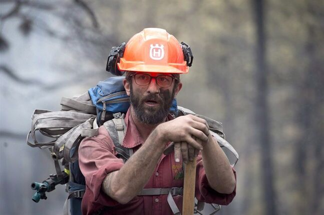 Firefighter Jake Sparks works at the Smith Creek fire in West Kelowna, B.C., on July, 19, 2014. THE CANADIAN PRESS/Jonathan Hayward