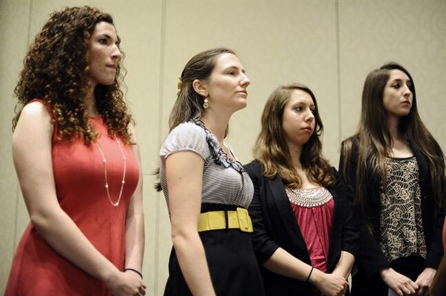 University of Connecticut students Rosemary Richi, left, Kylie Angell, second from left, Erica Daniels, second from right, and Carolyn Luby, right, listen to attorney Gloria Allred speak during a news conference, Friday, July 18, 2014, in Hartford, Conn. The University of Connecticut will pay nearly $1.3 million to settle a federal lawsuit filed by five women who claimed the school responded to their sexual assault complaints with indifference, the two sides announced Friday. (AP Photo/Jessica Hill)