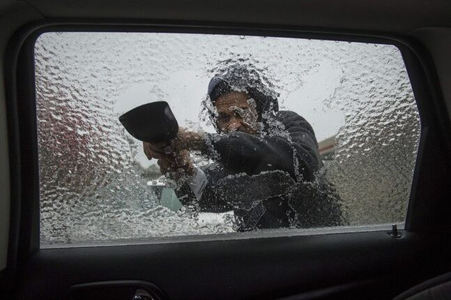 Lamarr Lewis scrapes ice from his car window during a winter storm on Wednesday, Feb. 12, 2014, in Doraville, Ga. (AP Photo/John Amis)