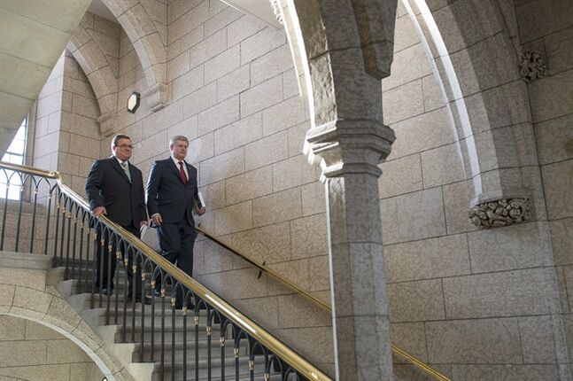 Prime Minister Stephen Harper arrives with Finance Minister Jim Flaherty as he enters the House of Commons to table the budget on Parliament Hill in Ottawa on Tuesday, Feb. 11, 2014. THE CANADIAN PRESS/Justin Tang