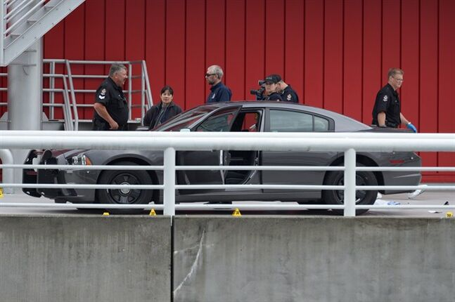 Police look at a police car after a shooting, near the area of Science World in Vancouver on Tuesday June 10, 2014. THE CANADIAN PRESS/Jonathan Hayward