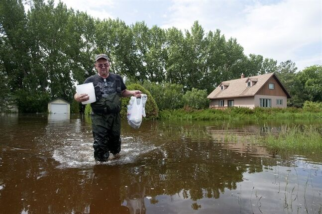 Murray Blakwill carries bags of food he recovered from his parents flooded home in Springside, Sask., Wednesday, July 2,2014. Nearly 90 communities in Saskatchewan and Manitoba have declared emergencies because of flooding and more than 500 people have been forced to leave their homes. THE CANADIAN PRESS/Liam Richards