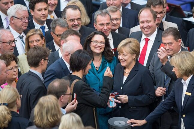 German chancellor Angela Merkel, center right, stands next to labor minister Andrea Nahles, center left, as they are surrounded by parliamentarians casting their vote in the German parliament, Bundestag, in Berlin Thursday July 3, 2014. The German Parliament has approved the introduction of the country's first national minimum wage, which will guarantee most workers in Europe's biggest economy at least 8.50 euros (US $11.60) per hour starting next year. (AP Photo/dpa, Maurizio Gambarini)