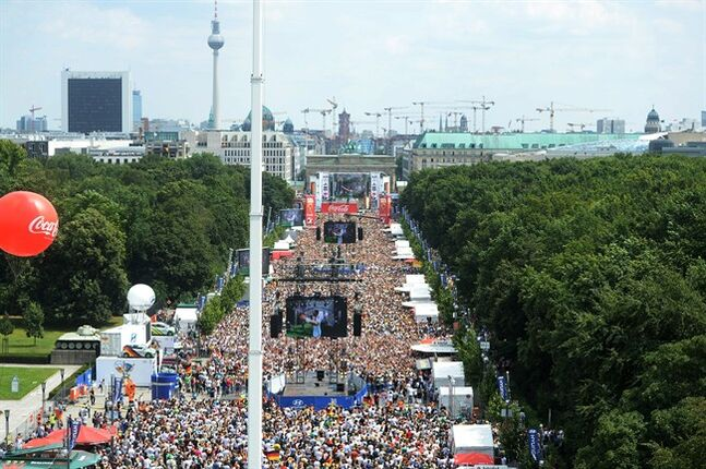 Soccer fans and supporters of the national soccer squad gather on the so called 'Fan Mile' near the Brandenburg Gate in Berlin , Tuesday July 15, 2014. Germany's World Cup winners shared their fourth title with hundreds of thousands of fans by parading the trophy through cheering throngs to celebrate at the Brandenburg Gate on Tuesday. An estimated 400,000 people packed the