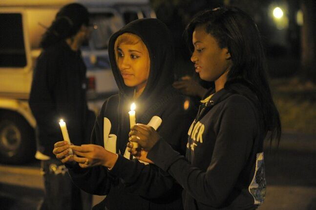 In this Wednesday, July 30, 2014 photo, Porscha Summers, 20, left, and Mykah Hall, 17, hold candles during a vigil for Jakari Pearson, who died from a gunshot wound, at the New Brewster Projects in Detroit's east side. Pearson was sleeping in his upstairs bedroom when�a bullet entered through a window and�struck him�in the chest. (AP Photo/Detroit News, Steve Perez)