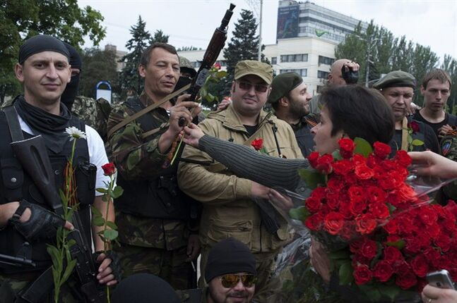 A woman gives flowers to pro-Russian fighters after the ceremony of taking the oath of allegiance to the self-proclaimed Donetsk People's Republic, on Lenin square in Donetsk, eastern Ukraine, Saturday, June 21, 2014. Dozens of pro-Russian armed militiamen gathered on Lenin square in Donetsk on Saturday to take the oath of allegiance to the so-called Donetsk People's Republic after Ukrainian President Petro Poroshenko ordered his forces to cease fire Friday and halt military operations for a week. (AP Photo/Evgeniy Maloletka)