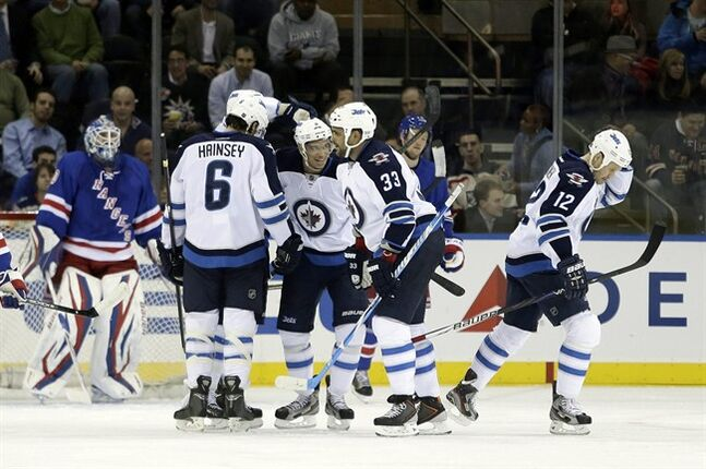 Winnipeg Jets players, including Ron Hainsey (6), Dustin Byfuglien (33) celebrate a goal by Olli Jokinen (12) during the second period of an NHL hockey game against the New York Rangers on Tuesday, Feb. 26, 2013, in New York. Rangers goalie Henrik Lundqvist, of Sweden, left, watches. (AP Photo/Frank Franklin II)