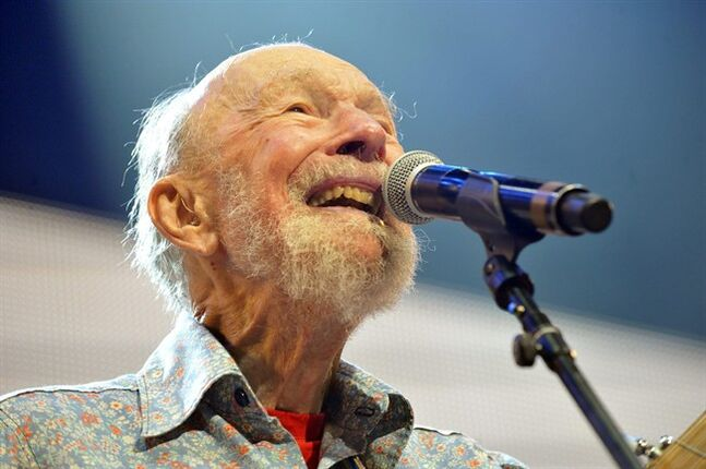 FILE - This Sept. 21, 2013, file photo shows Pete Seeger performing on stage during the Farm Aid 2013 concert at Saratoga Performing Arts Center in Saratoga Springs, N.Y. Lincoln Center says it will offer a live stream from a weekend memorial concert for Pete Seeger and his wife Toshi. The free concert will be held Sunday at Lincoln Center's Damrosch Park. It will feature artists and speakers who had a close personal relationship with the Seegers. They include Judy Collins, Harry Belafonte, Dar Williams, Peter Yarrow, Holly Near and Tom Chapin. (AP Photo/Hans Pennink, File)