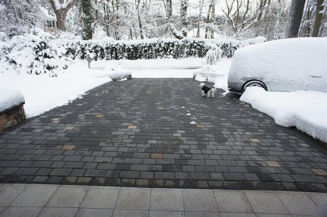 This undated photo provided by Warmzone, a Utah-based radiant heating company, shows a heated driveway and what it looks like in action after a big snow. After last year's rough winter, heated driveways are more popular than ever, with a rising number of homeowners putting away their shovels for good. (AP Photo/Warmzone)