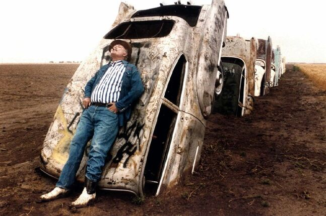 FILE - In this June 1984 file photo, Stanley Marsh 3 leans on one of the 10 Cadillacs buried down on his ranch west of Amarillo, Texas, along old Route 66. Stanley Marsh 3, whose partially buried row of Cadillacs became a road-side tourist attraction in the 1970s, died Tuesday, June 17, 2014. He was 76. (AP Photo/The Dallas Morning News, Evans Caglage, File) MANDATORY CREDIT; MAGS OUT; TV OUT; INTERNET OUT; AP MEMBERS ONLY
