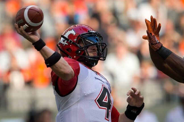Calgary Stampeders' quarterback Drew Tate, left, throws the ball away while being pressured by B.C. Lions' Jamall Johnson during the first half of a pre-season CFL football game in Vancouver, B.C., on Friday June 20, 2014. Aside from some suspense at quarterback, this season's Stampeders look similar to their 14-4 team of last year.THE CANADIAN PRESS/Darryl Dyck