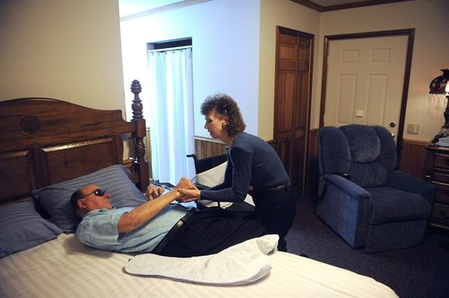 In this Aug. 30, 2013 photo, Pauline King cares for her husband Jerry King at their home in Anna, Ill. Jerry was diagnosed with Multiple Sclerosis in 1978. He can no longer go to the bathroom, bathe or dress himself without assistance from Pauline. You promise in sickness and in health, but a new poll shows becoming a caregiver to a frail spouse causes more stress than having to care for Mom, Dad or even the in-laws. Americans count on their families to care for them as they get older, with good reason: Half of people 40 and over already have been caregivers to relatives or friends, the poll found. (AP Photo/Stephen Lance Dennee)