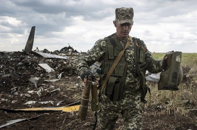 A pro-Russian fighter carries parts of weapons from the site of remnants of a downed Ukrainian army aircraft Il-76 at the airport near Luhansk, Ukraine, Saturday, June 14, 2014. Pro-Russian separatists shot down the military transport plane Saturday in the country's restive east, killing all 49 service personnel on board, Ukrainian officials said. (AP Photo/Evgeniy Maloletka)