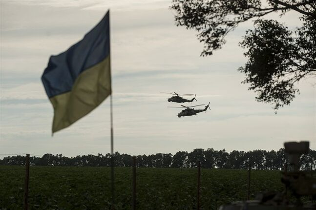 Two Ukrainian military helicopters carry Ukrainian President Petro Poroshenko and Minister of Defense Valery Heletey to inspect weapons captured from rebels at the base in Devhenke village, Kharkiv region, eastern Ukraine, Tuesday, July 8, 2014, with a Ukrainian national flag in the foreground. President Petro Poroshenko has suggested, that mediation could take place in a government-controlled town some 220 kilometers west of Russia_ a proposal staunchly rejected by the rebels. (AP Photo/Evgeniy Maloletka)
