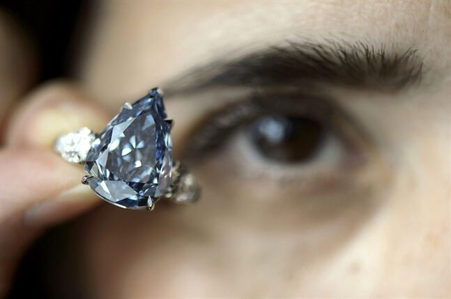 FILE - In this May 9, 2014 file picture a Christie's employee holds a 13.22 carat diamond called 'The Blue', the largest flawless vivid blue diamond yet found, which is estimated to sell between US dlrs 21 to 25 million , during a preview at Christie's, in Geneva, Switzerland. The auction will take place on Wednesday May 14, 2014 evening in Geneva. (AP Photo/Keystone, Martial Trezzini,file)