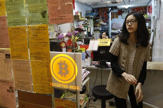 A staff member from a travel agency displays a Bitcoin logo as they accept bitcoins for payment in Hong Kong Friday, Feb. 28, 2014. The world's first bitcoin retail store opened in Hong Kong on Friday, despite the virtual currency facing much scrutiny over the last week. (AP Photo/Kin Cheung)