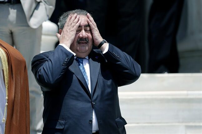 Iraqi Foreign Minister Hoshyar Zebari reacts to the heat before a group photo during an EU-Arab league Foreign Ministers summit in Athens, on Wednesday, June 11, 2014. The fall of the major northern Iraqi city of Mosul to insurgents must push the country's leaders to work together and deal with the