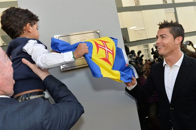 Cristiano Ronaldo and his son Cristiano Junior, held by the Madeira island regional government president, Alberto Joao Jardim, unveil a plaque during the inauguration of Ronaldo's museum in Funchal, Portugal, Sunday, Dec. 15 2013. The museum displays 150 of the soccer player's trophies and awards. (AP Photo/Joana Sousa)