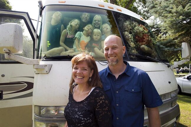 The Kelloggs pose for a photo as 11 of their 12 children ham it up in the window of their RV in Toronto on Friday August 1, 2014. In less than two years, Dan and Susie Kellogg have logged tens of thousands of kilometres in their RV, and they've had plenty of company along for the ride: their 12 children. THE CANADIAN PRESS/Frank Gunn
