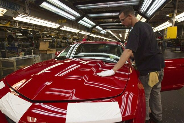 In this June 10, 2011, a worker checks the paint on a Camaro at the GM factory in Oshawa, Ontario. THE CANADIAN PRESS/AP, Frank Gunn