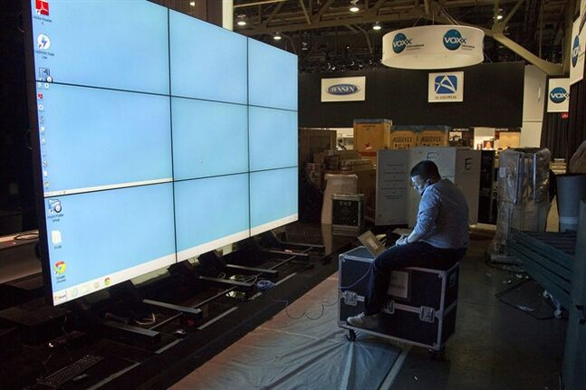 Sharp Electronics employee Michael Nenortas programs a flat screen display at the company's show booth Jan. 6, 2013, in Las Vegas. THE CANADIAN PRESS/AP, Julie Jacobson