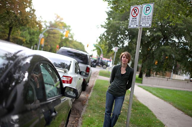 Fourth-year student Alexandra Daum stands under a two-hour parking sign on Princess Avenue adjacent to Brandon University on Thursday. Many BU students are frustrated by a lack of parking available around the campus and say that the maximum two-hour parking offered on city streets in the area is ineffective when students have three-hour classes.