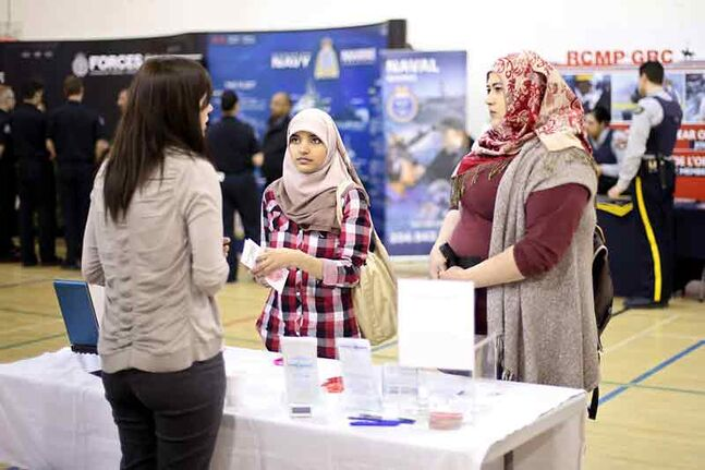 Munzaleen Sajjad and Boshra Mohammed speak with Camilla Harkness with West-Can Human Resources Solutions during the career fair at Assiniboine Community College's Victoria Avenue East campus on Thursday.