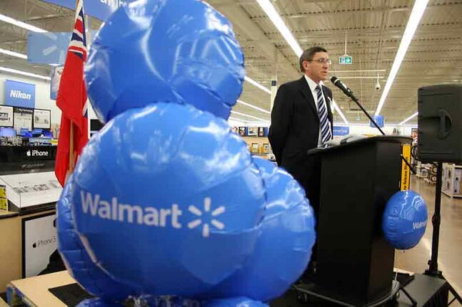 Walmart store manager Michael Humenny speaks to a crowd of around 100 people during the store's grand reopening at the Walmart Supercentre on Friday.