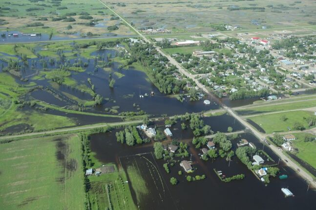 Water inundates the community of Reston, Manitoba, flooding homes on the west side of the community as seen from the air on Wednesday.