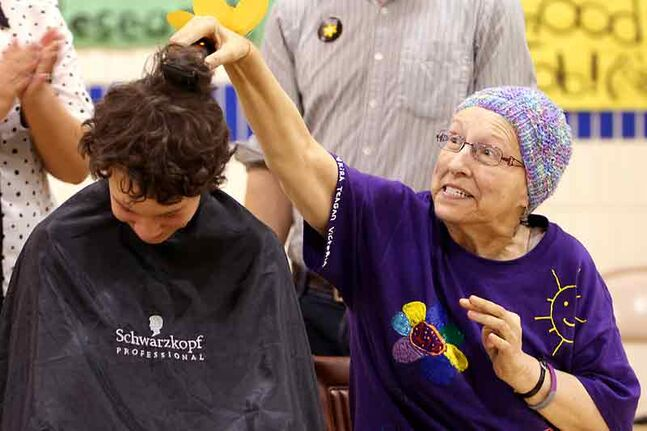 Elizabeth Grant shaves the first strip of hair off  Michael Wenham, 14, during an assembly at King George School in April. Wenham raised $8,414 for the Canadian Cancer Society in Grant's honour in advance of the event.