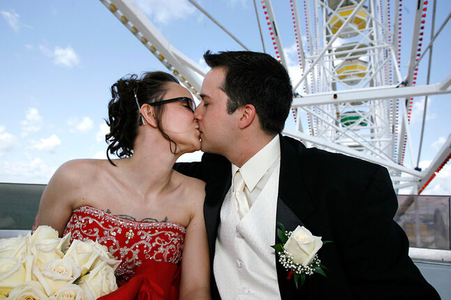 In this June 2007 photo, a couple  kisses while on a  Ferris wheel ride after getting married at Winnipeg's Red River Ex. A report released by the Institute of Marriage and Family Canada says wealthy people are typically married or in  common-law unions, while the poor are mostly unattached.