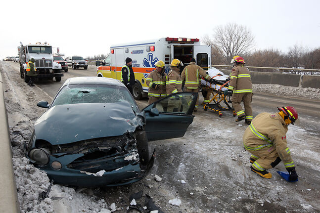 In this December 2013 photo, Brandon Fire and Emergency Services members move a patient on a stretcher to a waiting ambulance after a two-vehicle collision on the Daly Overpass. In addition to provincial funding, the city is also looking to secure federal cash to complete the expansion of the overpass.
