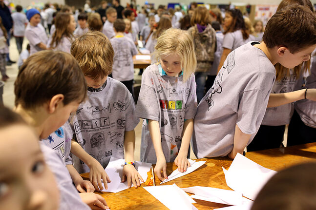 Hannah Leckie, a Grade 4 student from Kirkcaldy Heights School, works on a paper airplane with other students at a activity station during the Western Manitoba Science Fair at the Keystone Centre on Tuesday.