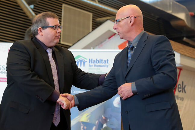 Assiniboine Community College president Mark Frison, left, and Habitat for Humanity Manitoba CEO Sandy Hopkins shake hands after signing a memorandum of understanding at the Len Evans Centre for Trades and Technology at ACC's North Hill Campus on Thursday.