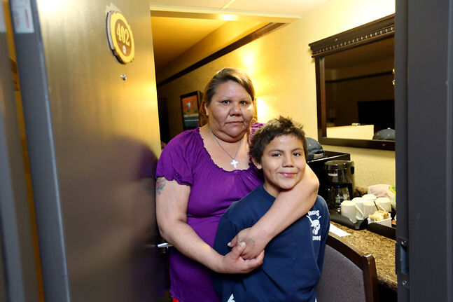 Teresa Davis of Waywayseecappo First Nation stands with her nine-year-old son Ty in the doorway to their room at the Russell Inn on Monday afternoon after being evacuated from their home on Saturday. Davis has a family of six staying in the room.