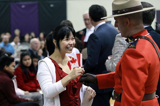 Blaikie, originally from Taiwan, accepts a flag after becoming a Canadian citizen during the last citizenship ceremony held in Brandon, at Vincent Massey High School in October 2012.