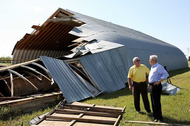 Premier Greg Selinger looks over the destroyed skating rink in Pipestone while getting a tour from RM of Pipestone Reeve Ross Tycoles after a storm ravaged the village last July.