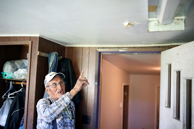 Sioux Valley Dakota Nation elder Albert Taylor points to where his ceiling leaks while speaking about his frustrations in getting help for the damage his home sustained during the tornado that struck the community last summer.