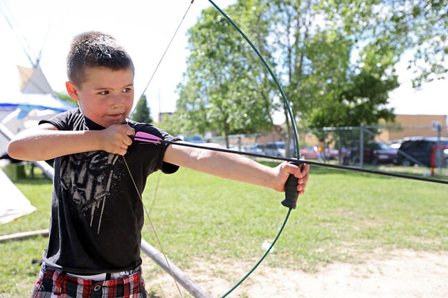 Jordan Soulier, 7, tries his hand at archery during Saturday's festivities at École New Era School.