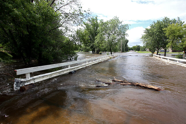 The swollen Gopher Creek in Virden flows over a bridge on Monday.