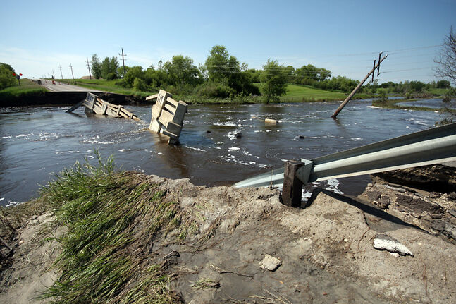 Water flows on Friday over debris from a bridge on Highway 445 in Melita that was washed out in this month's flooding.