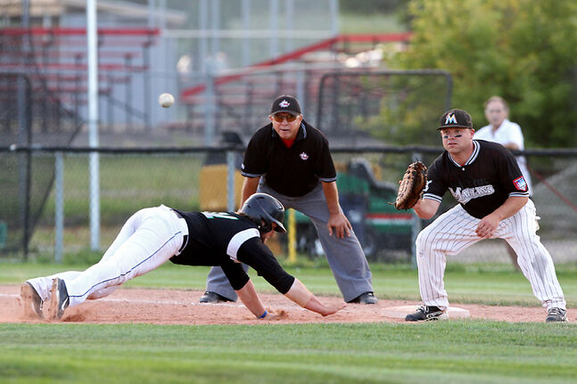 Travis Jean of the Brandon Cloverleafs dives back to first base before the ball can make it to Ryan Boguski of the Brandon Marlins during Game 4 of their MSBL championship series at Andrews Field on Tuesday evening. The Marlins won 10-9.