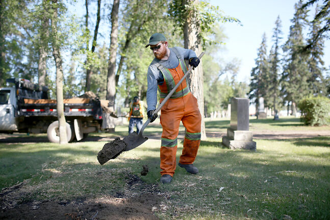 Ryan Moody with the City of Brandon fills in a hole, created after a tree fell during July's storm, at the Brandon Municipal Cemetery on Thursday.